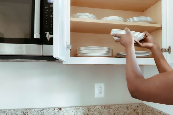 Woman Puts Dishes Into Kitchen Cabinet