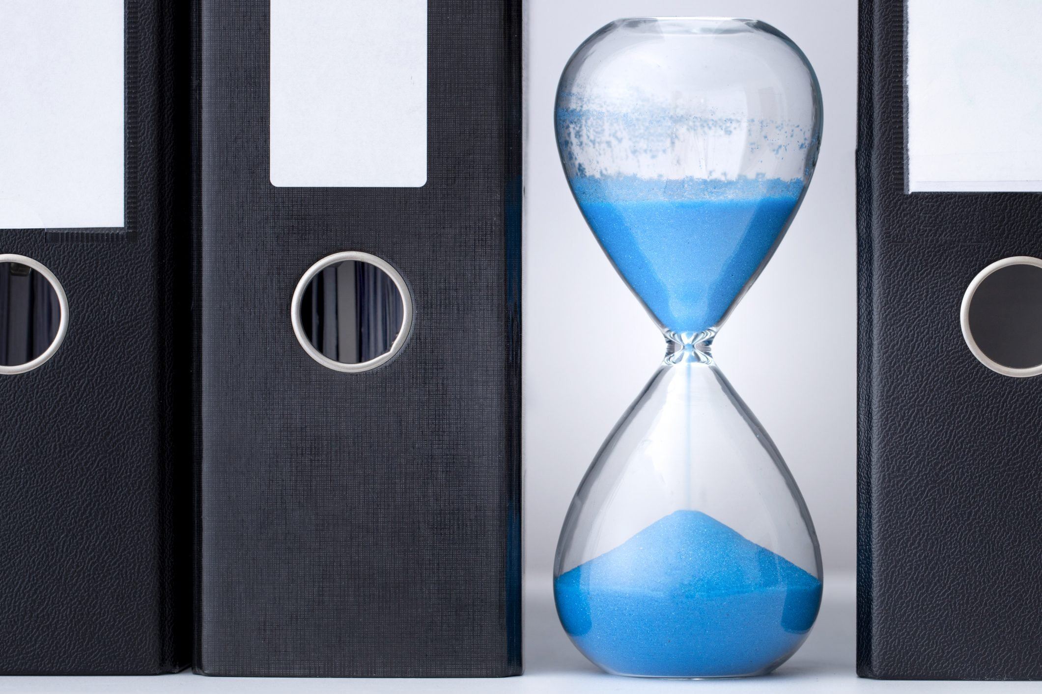 Blue hourglass, half expired, stands between a row of files