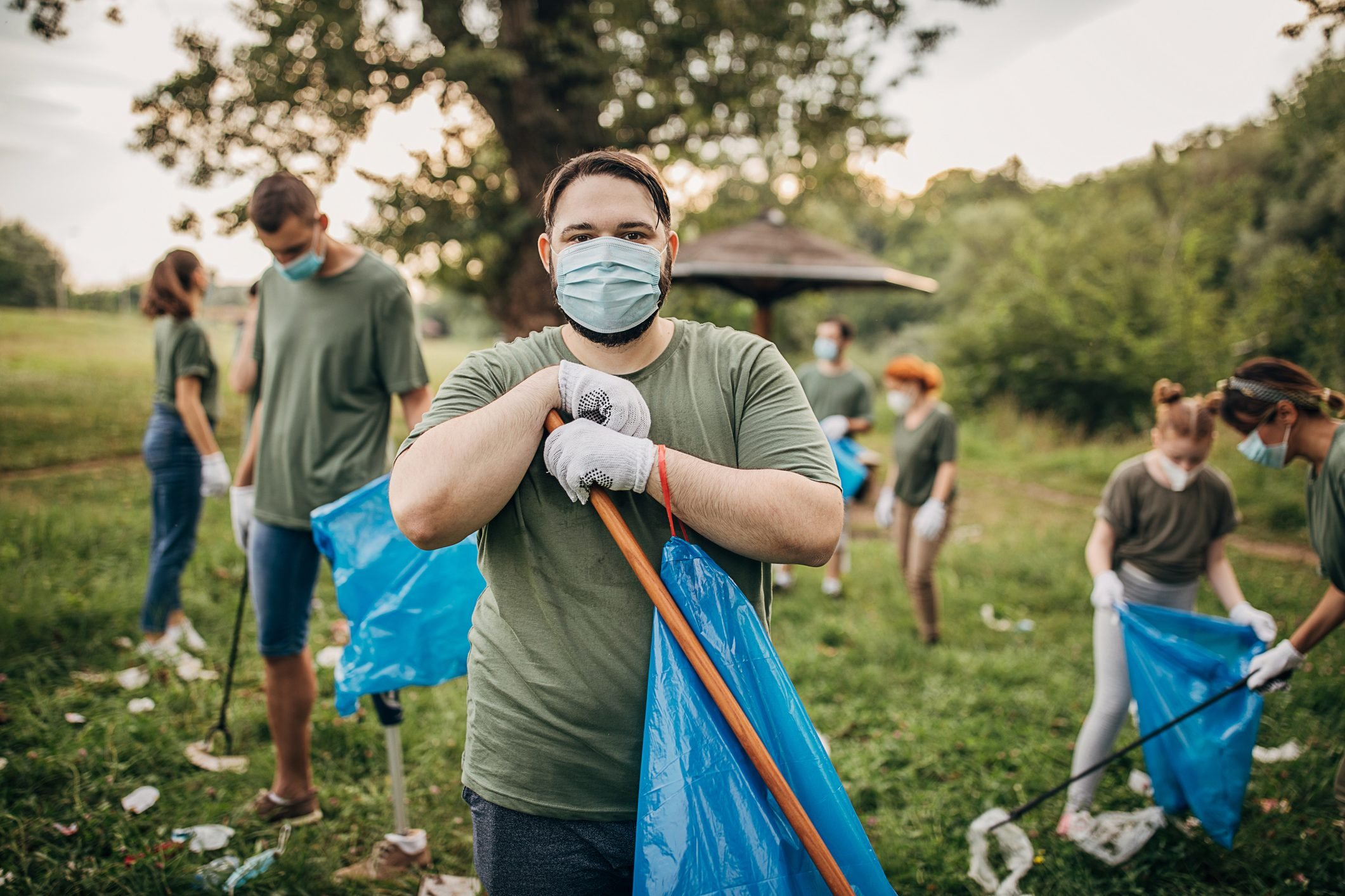 Portrait of man with group of volunteers with surgical masks cleaning nature together