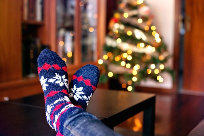Close-up of feet in warm winter socks near the Christmas tree with its lights on