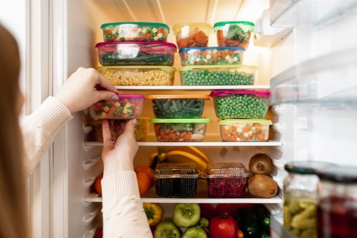 Woman taking raw food from refrigerator
