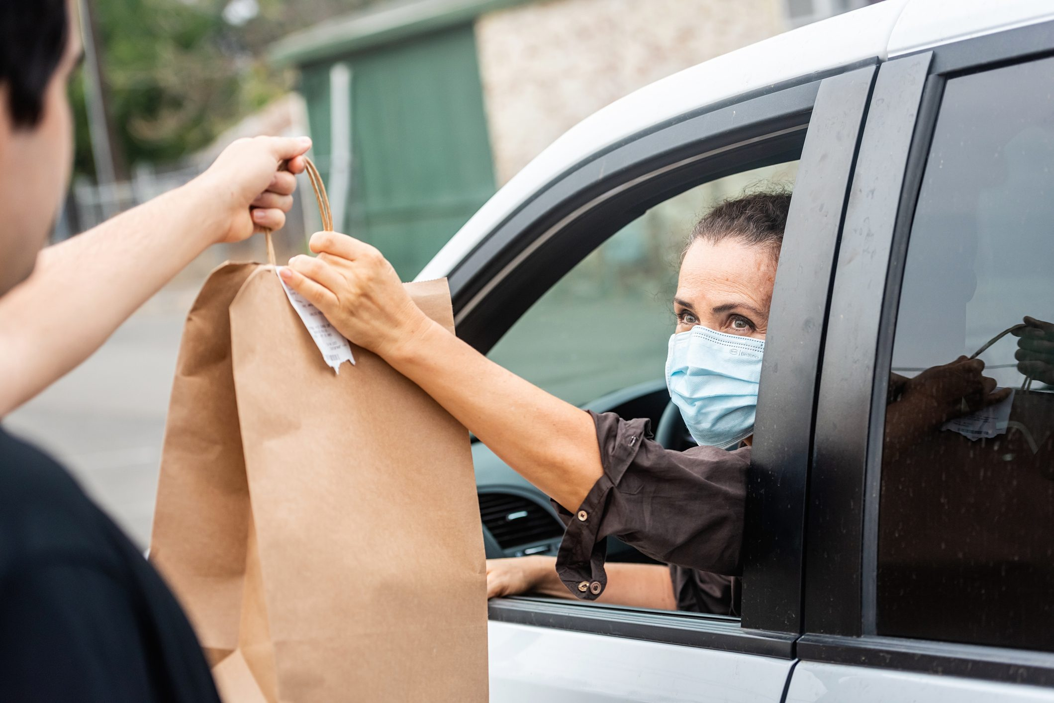 Mature woman picking her to go order from her car at a Curbside pickup