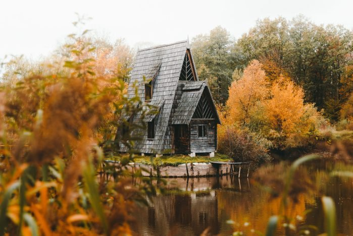 """Scenic view of the """"A"""" frame wooden cabin at the reflection lake at the forest in autumn colors"""