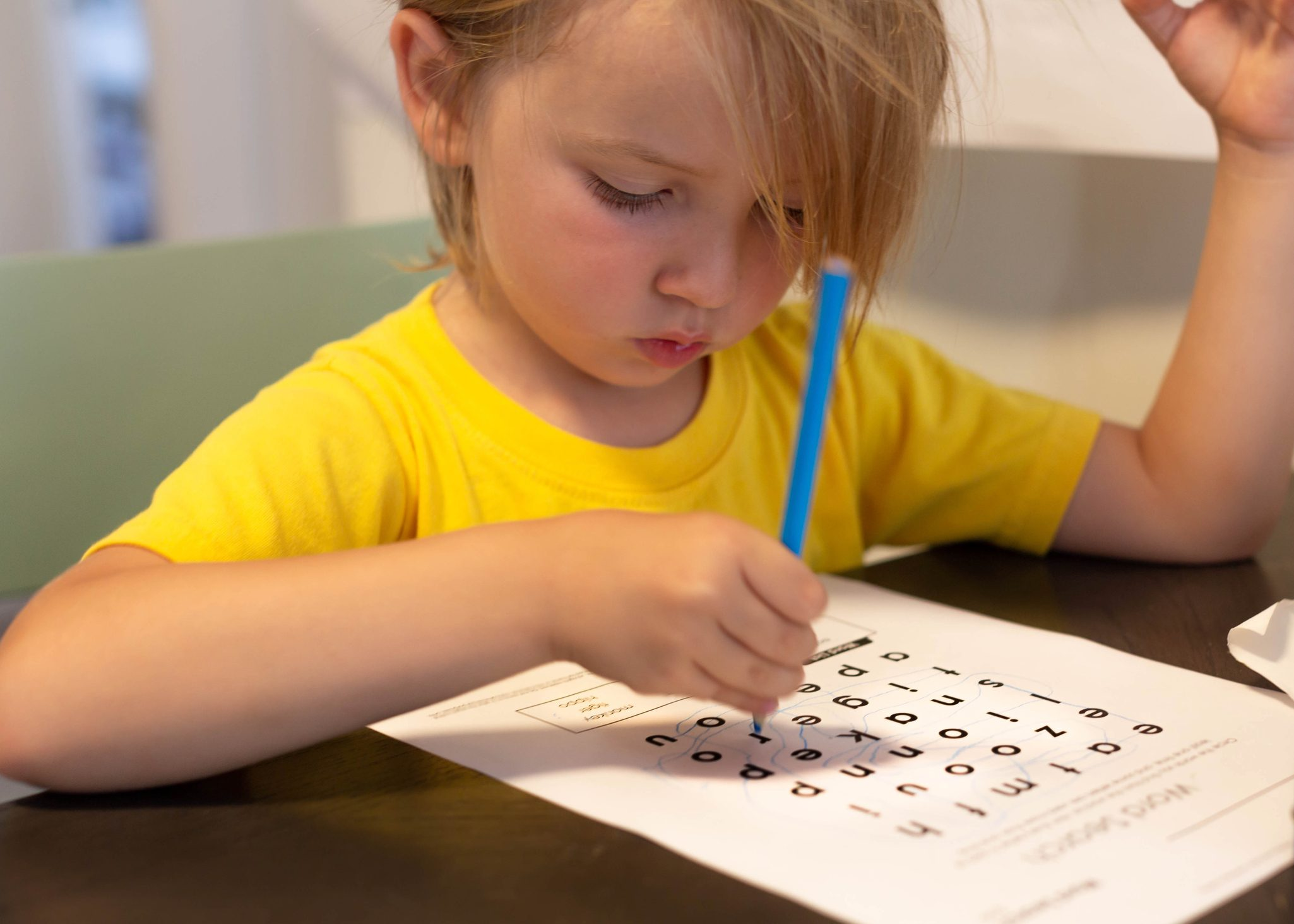 A young kid doing school work at home. Learning words.