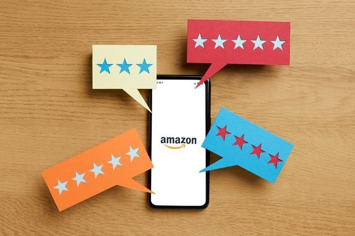 amazon app opening on a phone with speech bubbles of stars around it to represent reviews on a wood table background