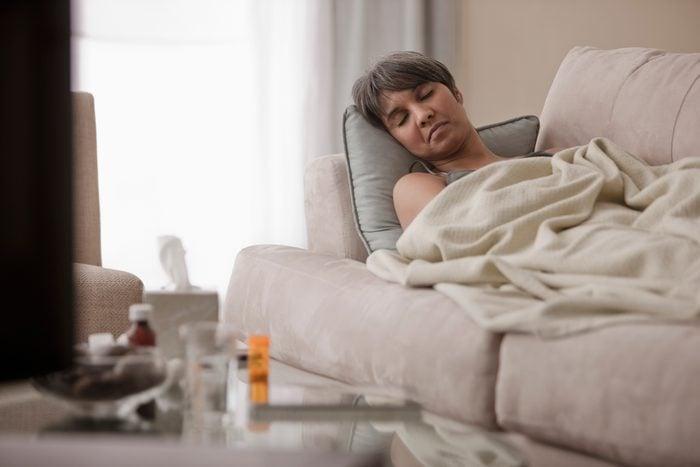Sick mixed race woman laying on sofa