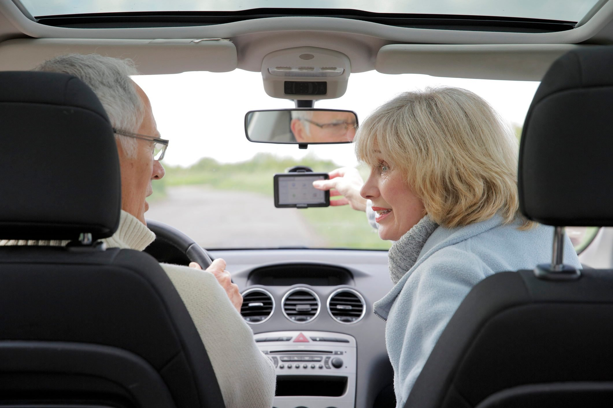 Mature couple using in a car using sat nav