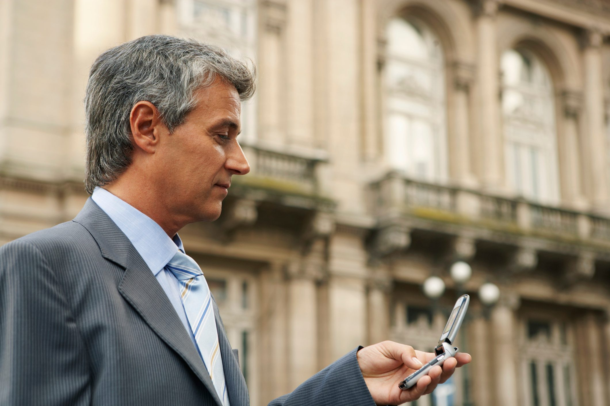 Mature businessman using mobile phone, close up, side view