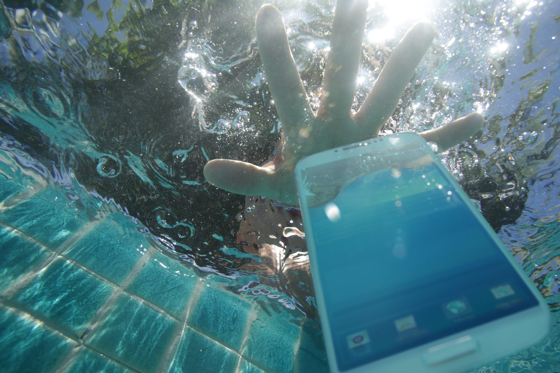 Hand reaching for phone dropped in pool