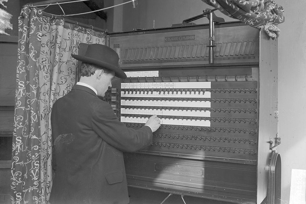 Man Standing In A Voting Machine