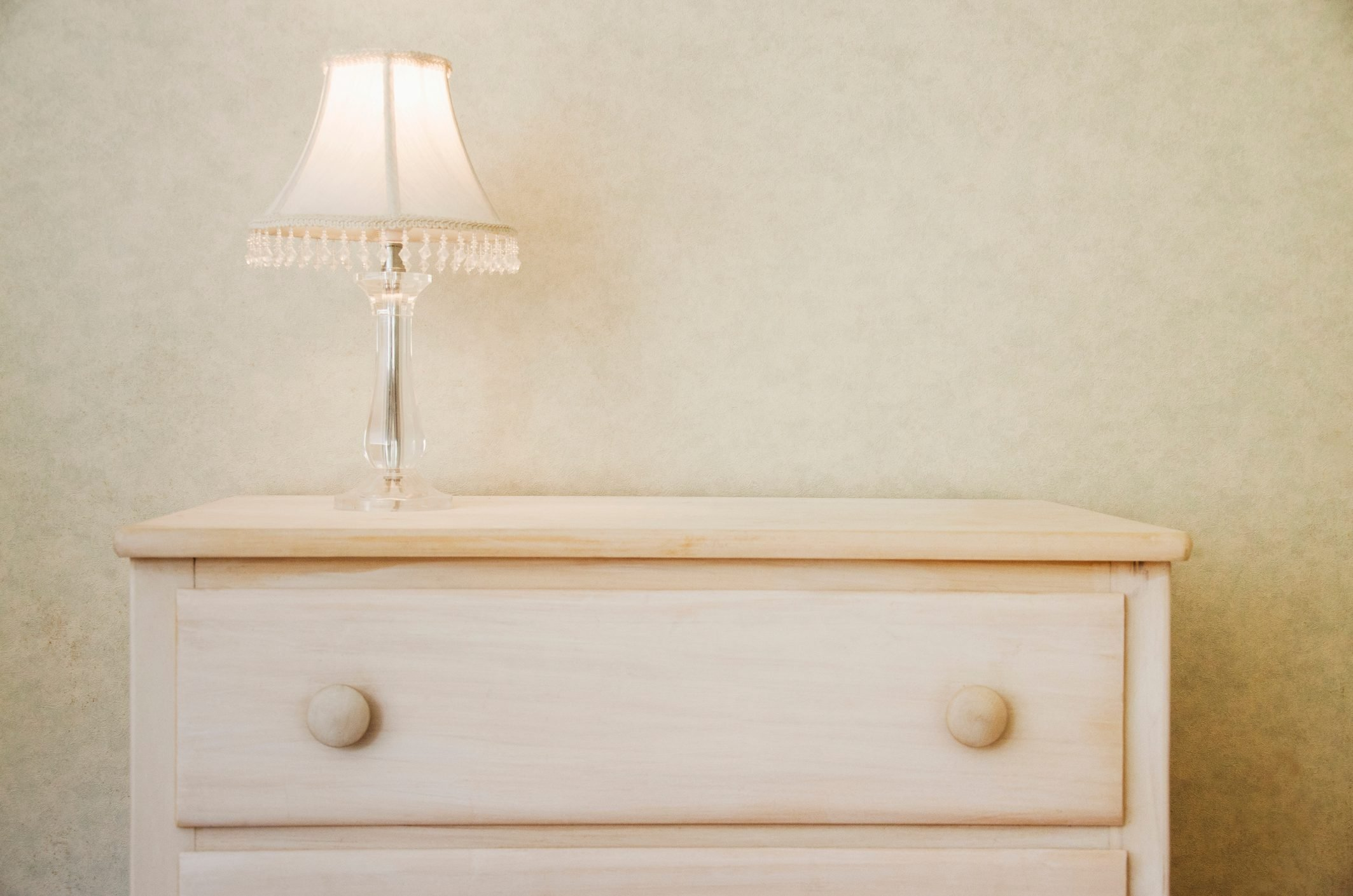 Electric lamp on wooden dresser