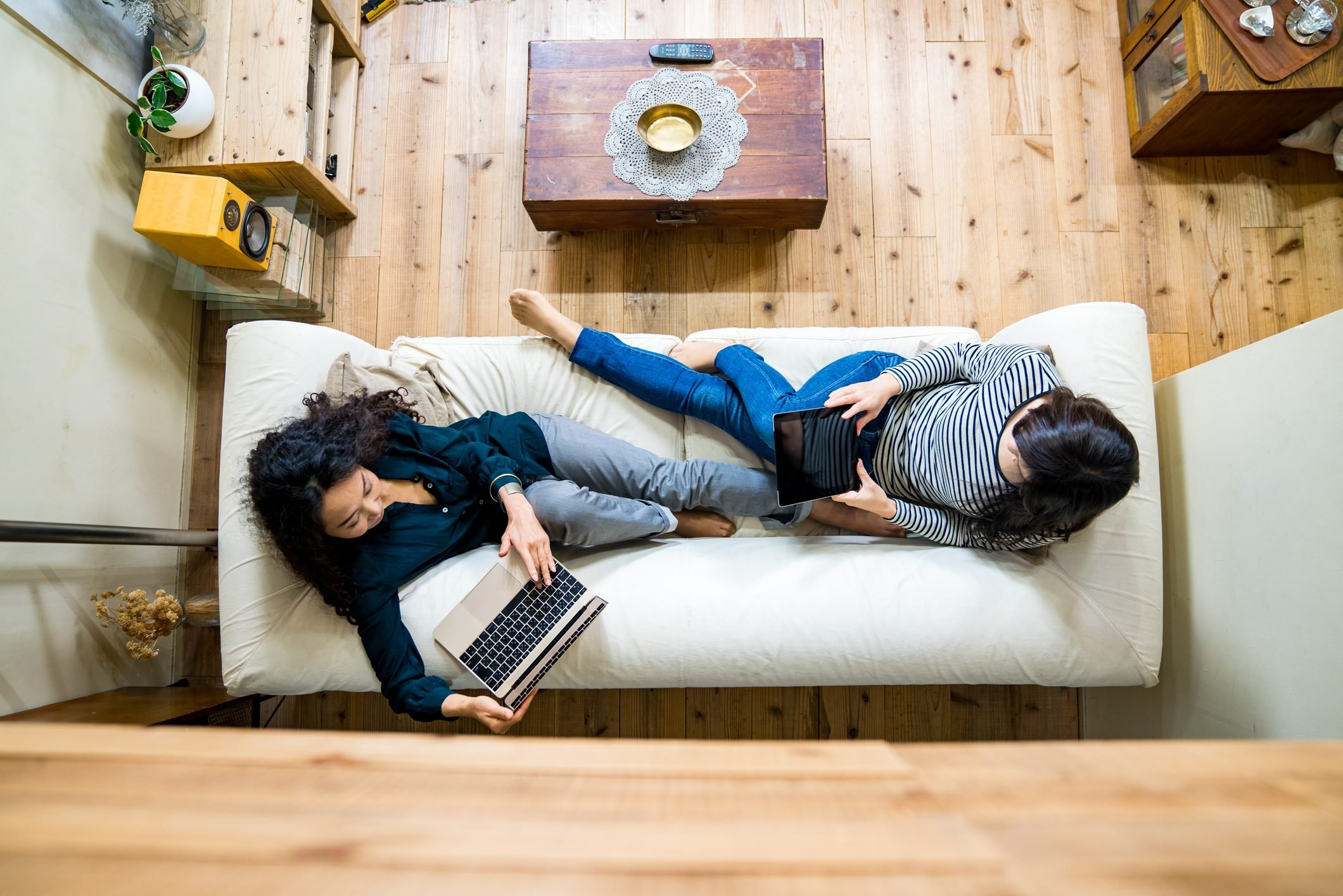 Mother and daughter laying on the sofa using smart devices