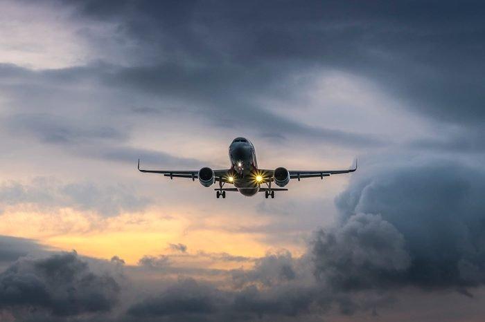 Airplane landing in dramatic sunset