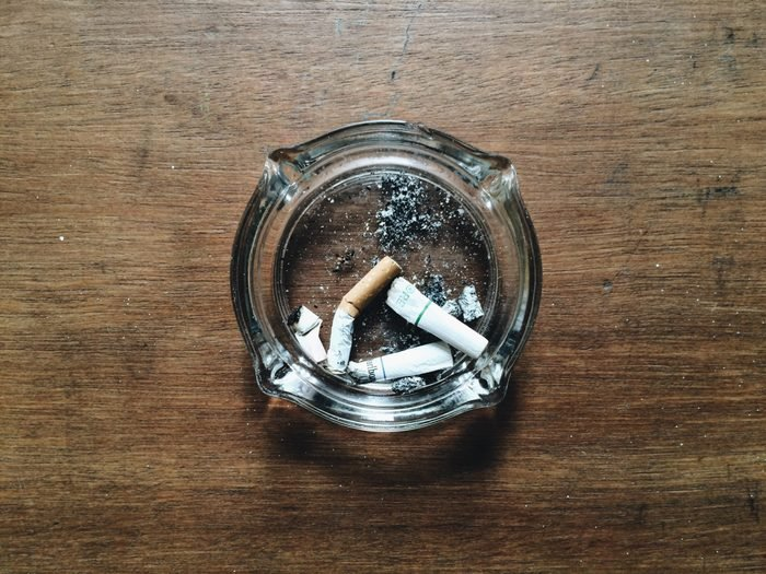 Directly Above Shot Of Cigarette Buts In Ashtray On Table
