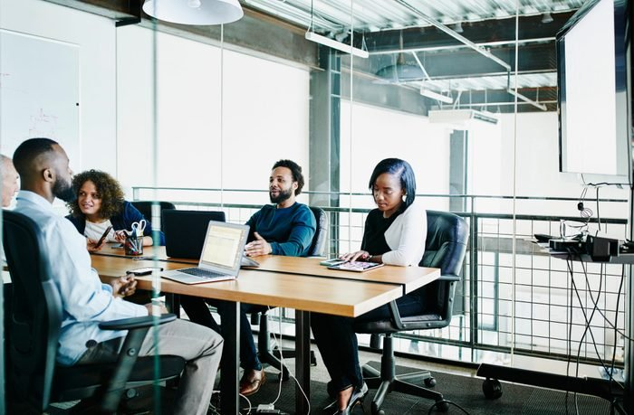 Coworkers having team meeting in office conference room