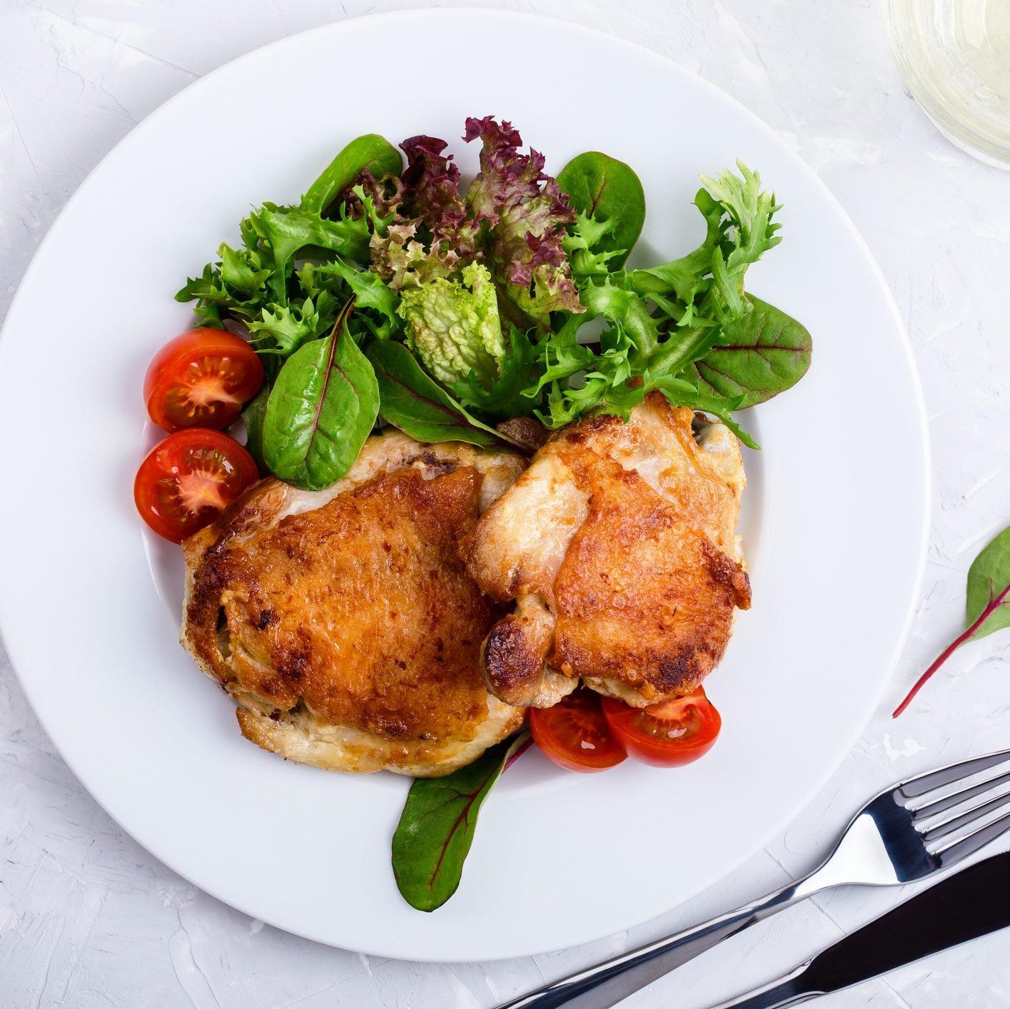 Roast chicken legs on white plate over light gray plaster texture table