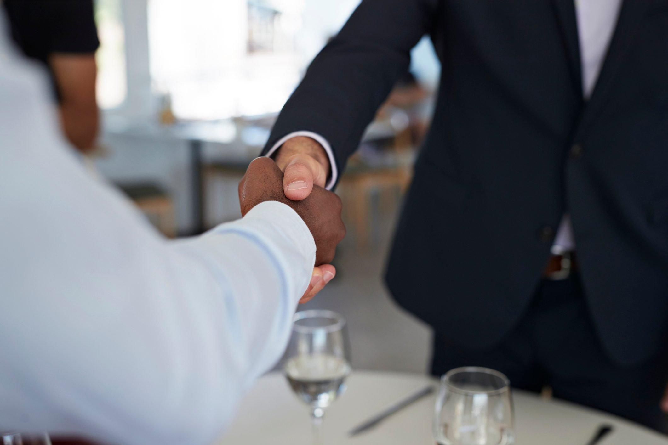 Businesspeople making handshakes, at restaurant