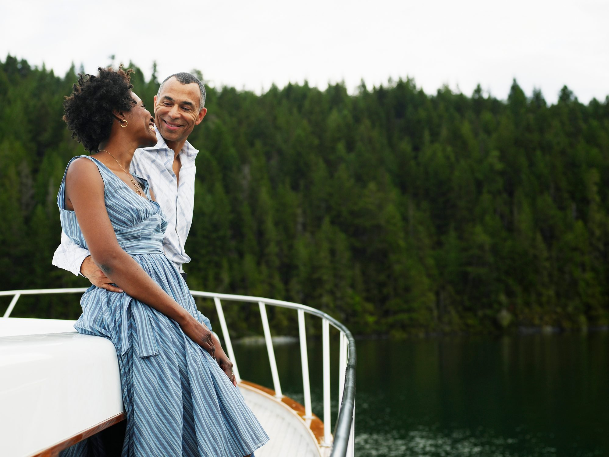 Mature man with arm around woman on yacht, smiling