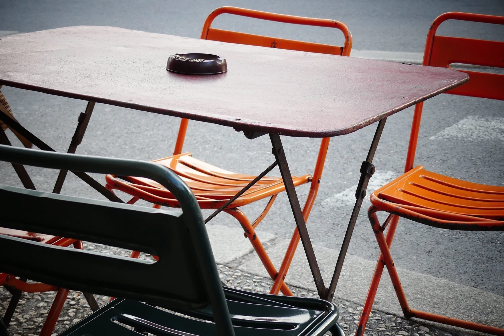 Close-Up Of Empty Chairs And Table At Sidewalk Cafe