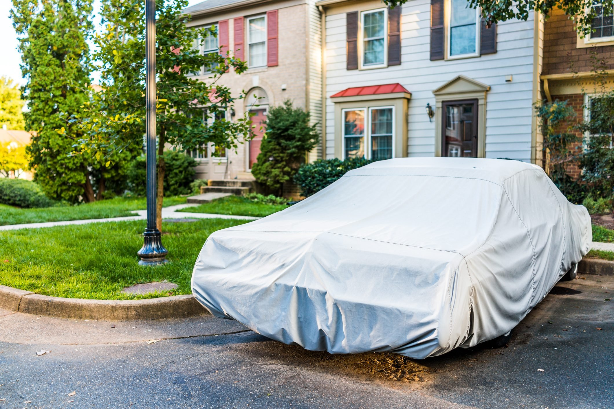 Vintage car covered with protective cover by townhouse for wet weather in parking lot