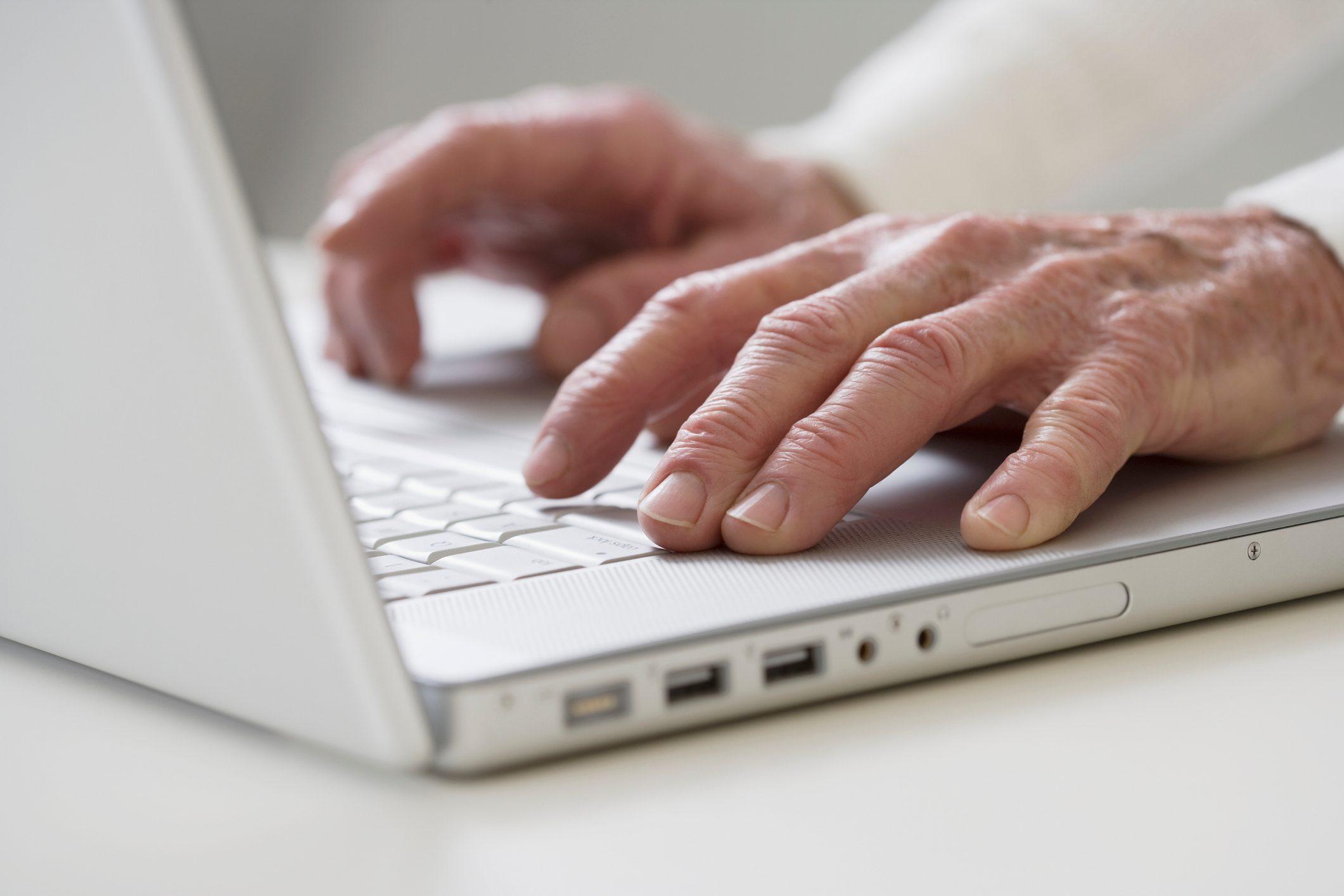 Close up of senior Hispanic man typing on computer