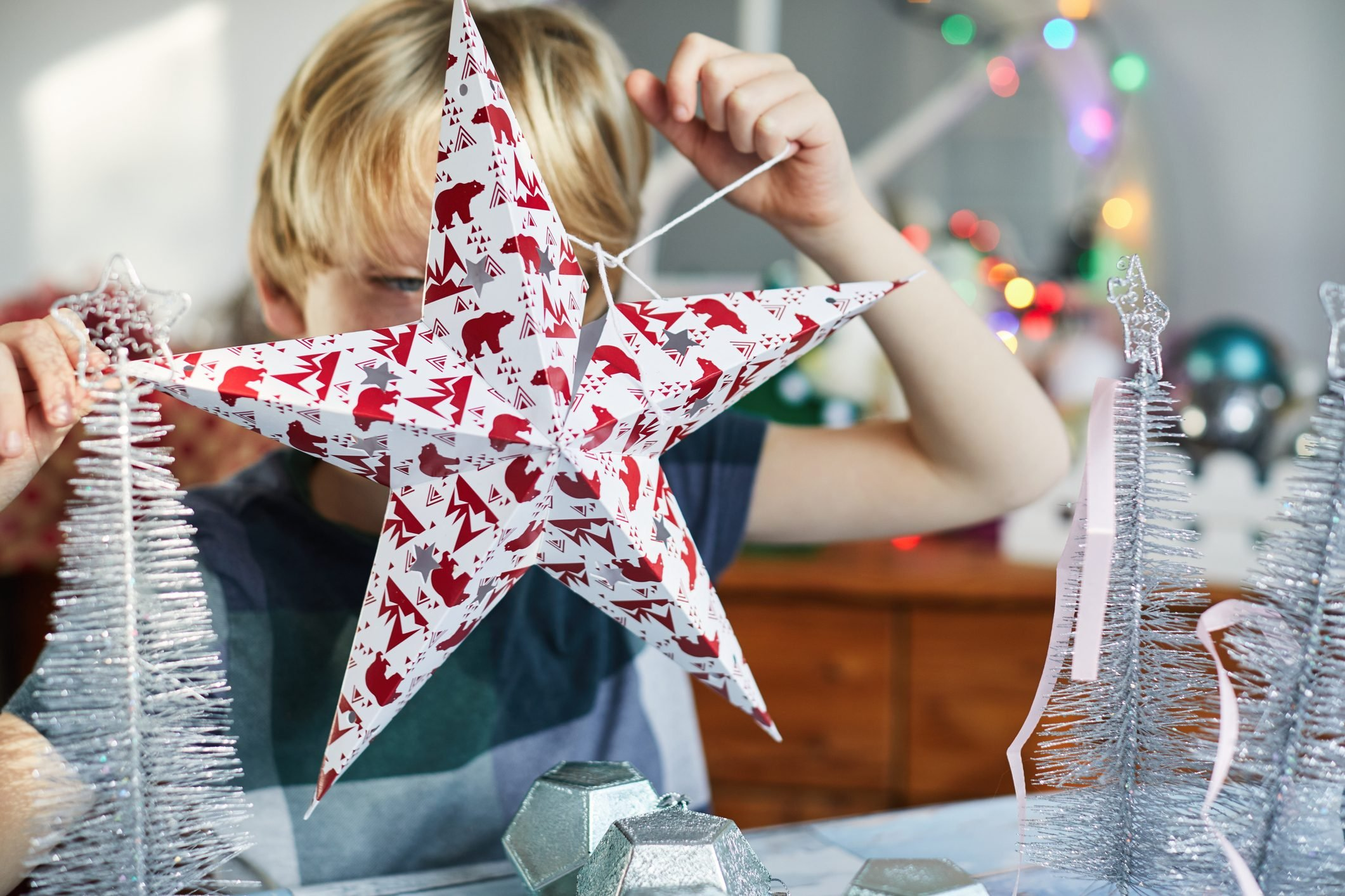 Child holding up a star Christmas decoration