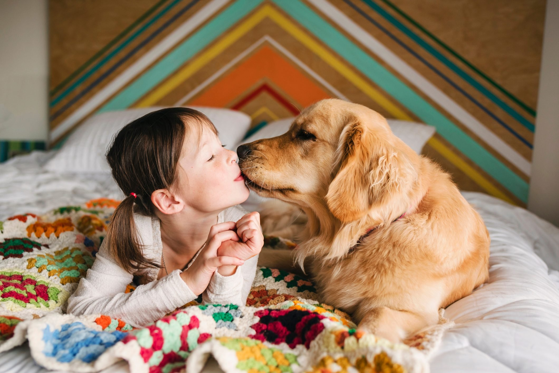 Girl lying on a bed kissing her golden retriever dog
