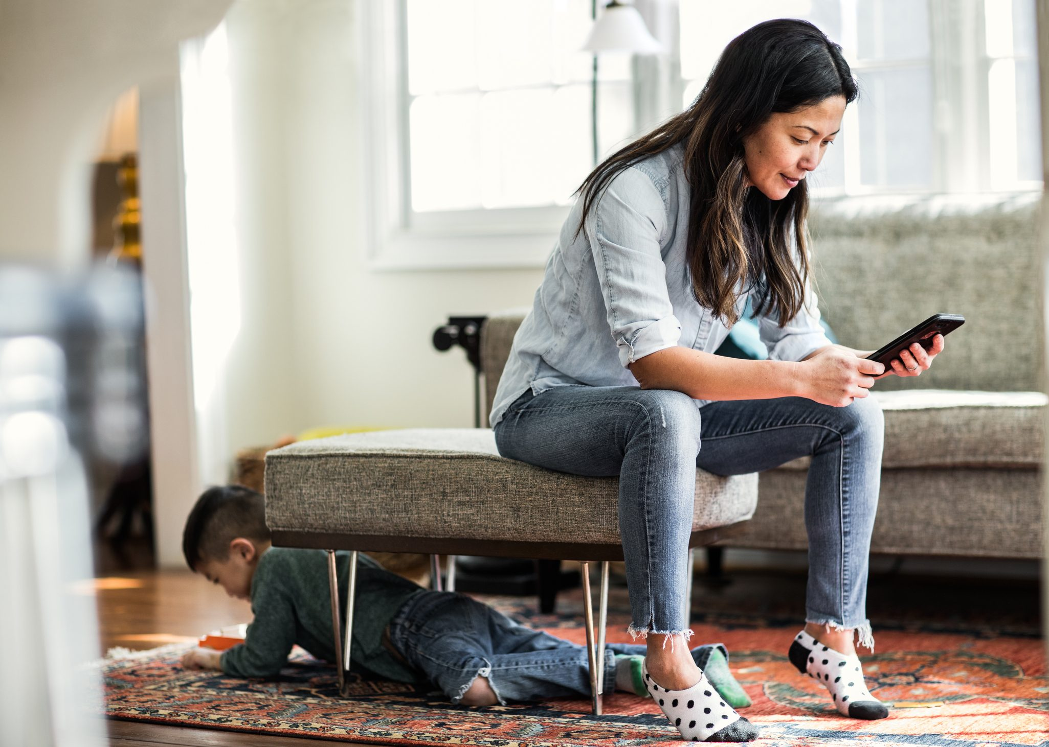 Woman using smartphone at home with child in background