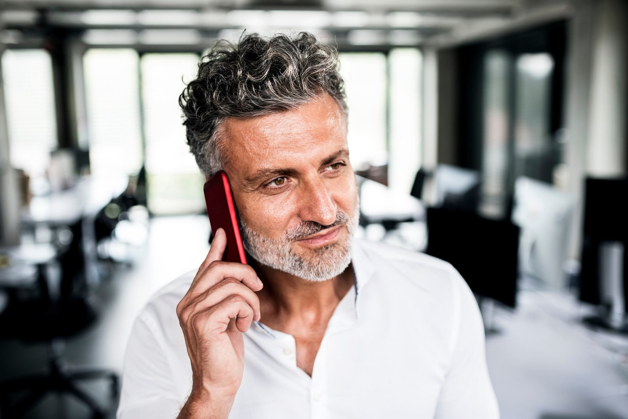Portrait of mature businessman on cell phone in office