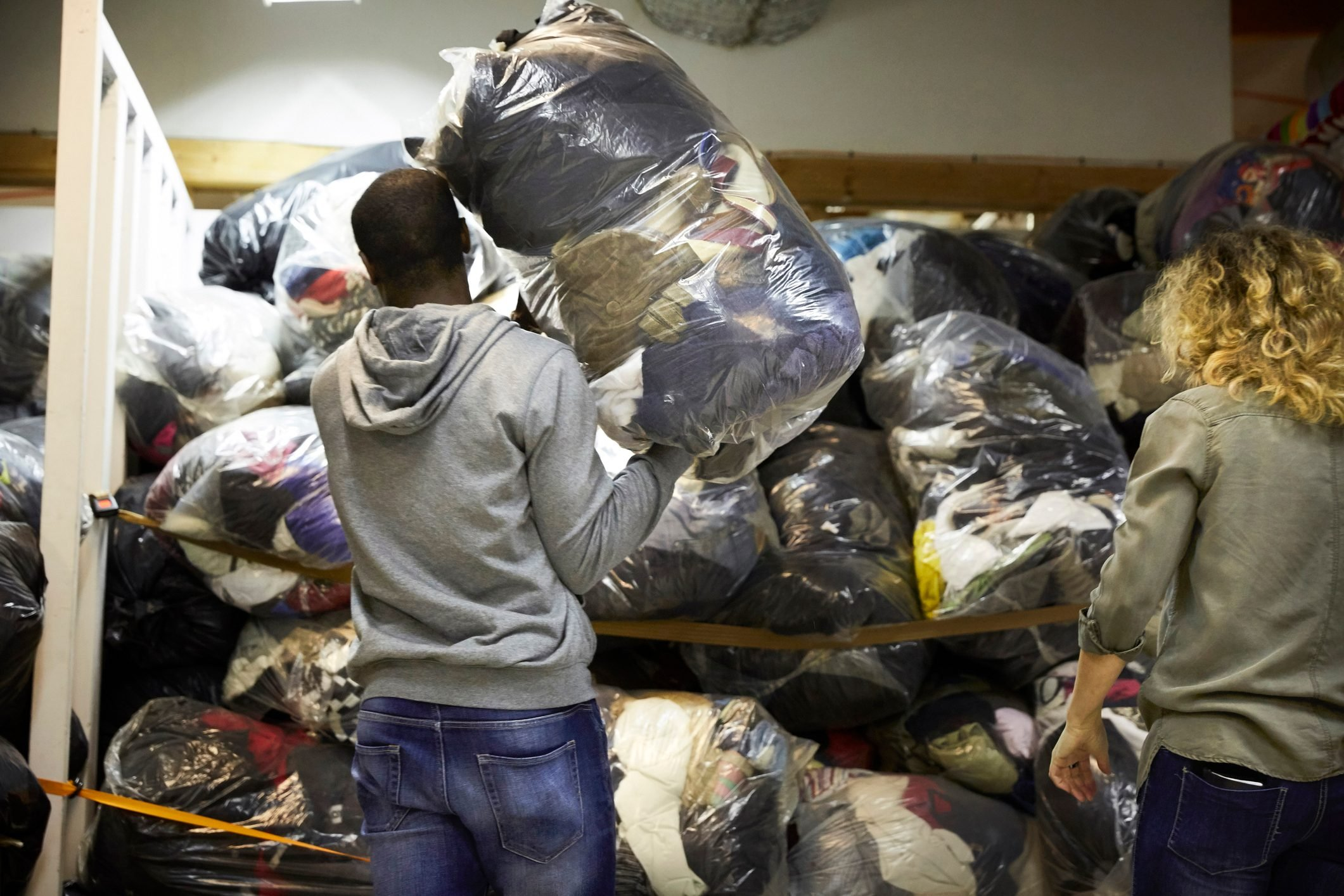 Rear view of coworkers stacking plastic sacks in warehouse