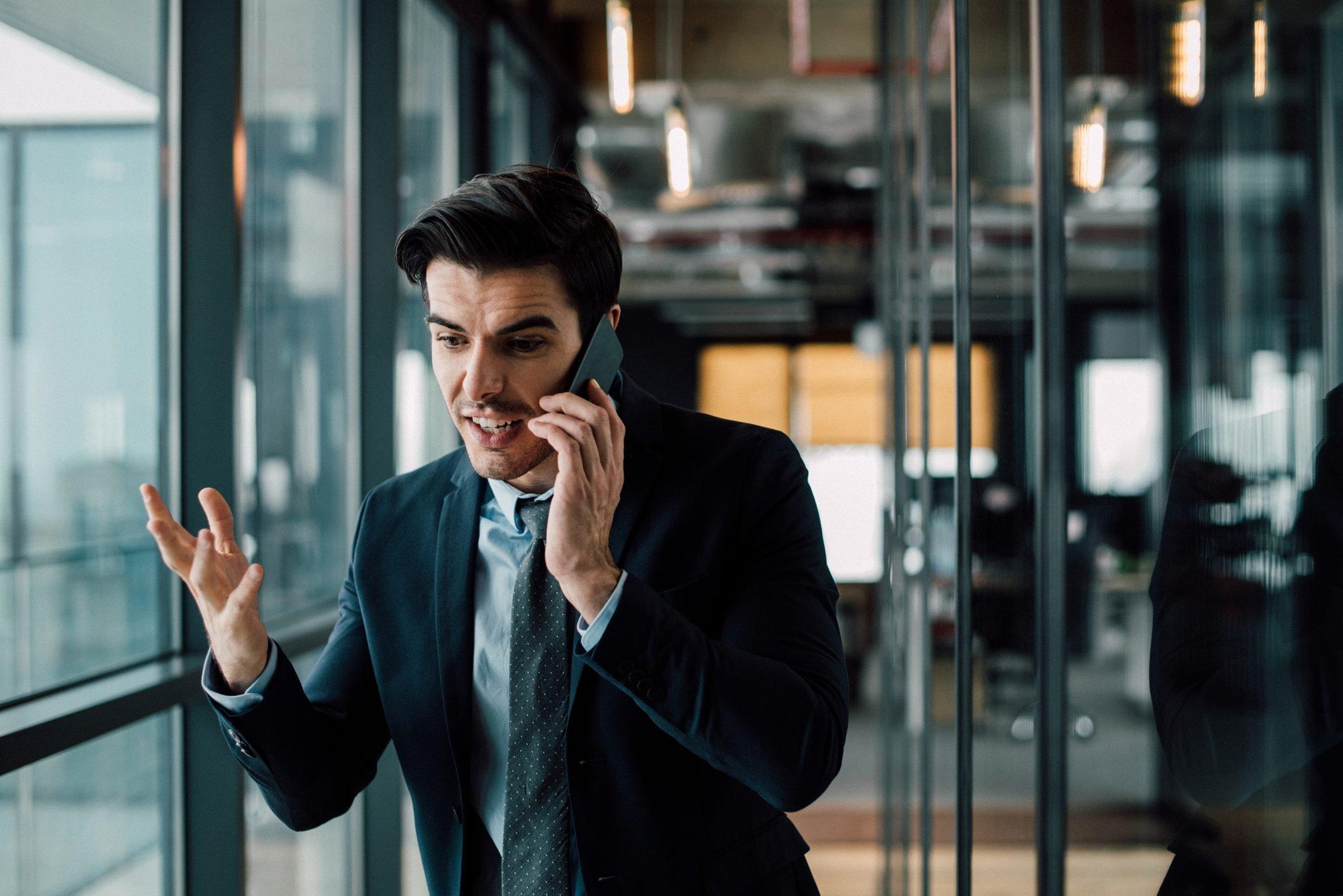 Amazed businessman annoyed with phone call