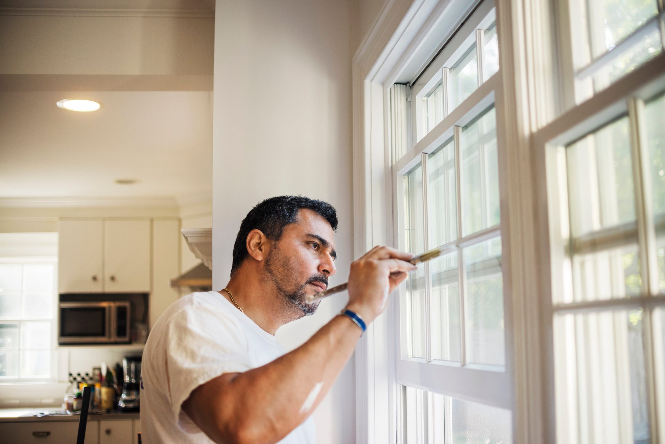 Side view of man painting window frame at home