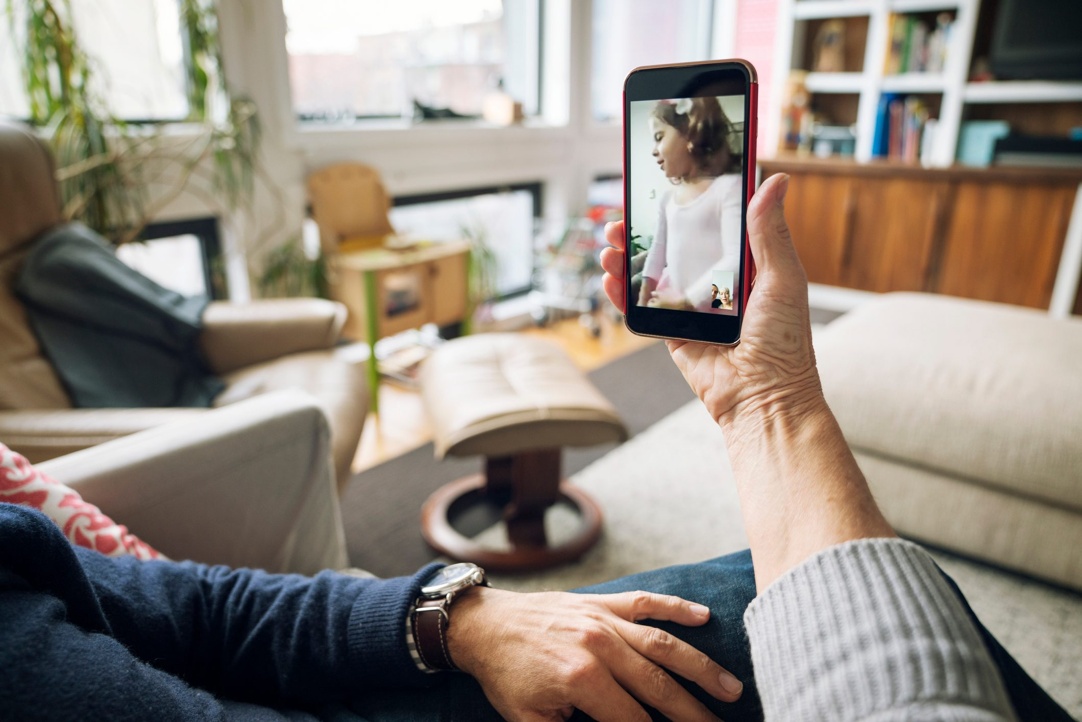 Cropped image of senior couple video conferencing at home