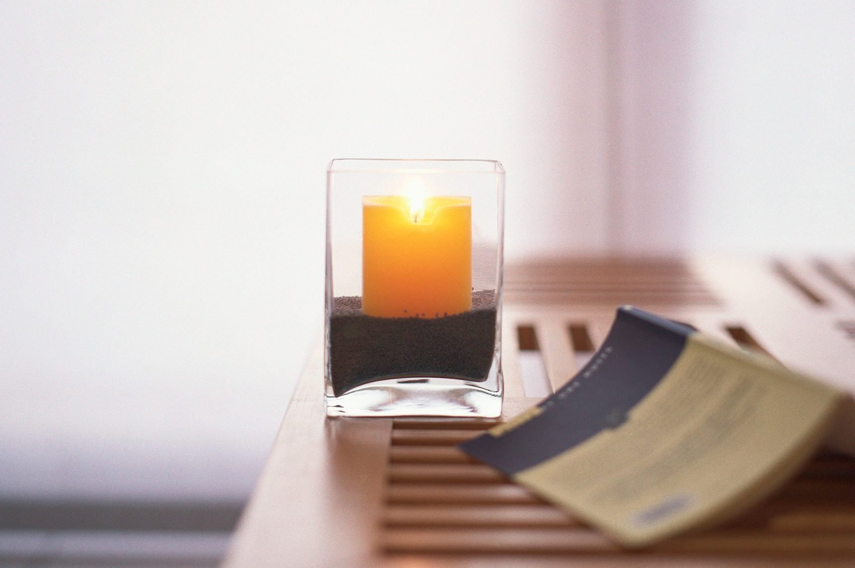 Candle and open book on table inside.