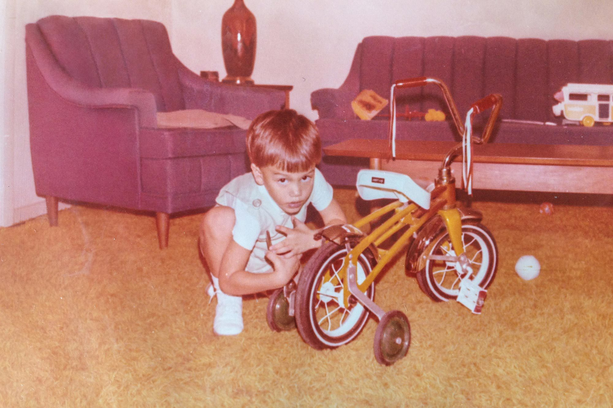 photo from Tom's childhood of him and his bike at the time with training wheels