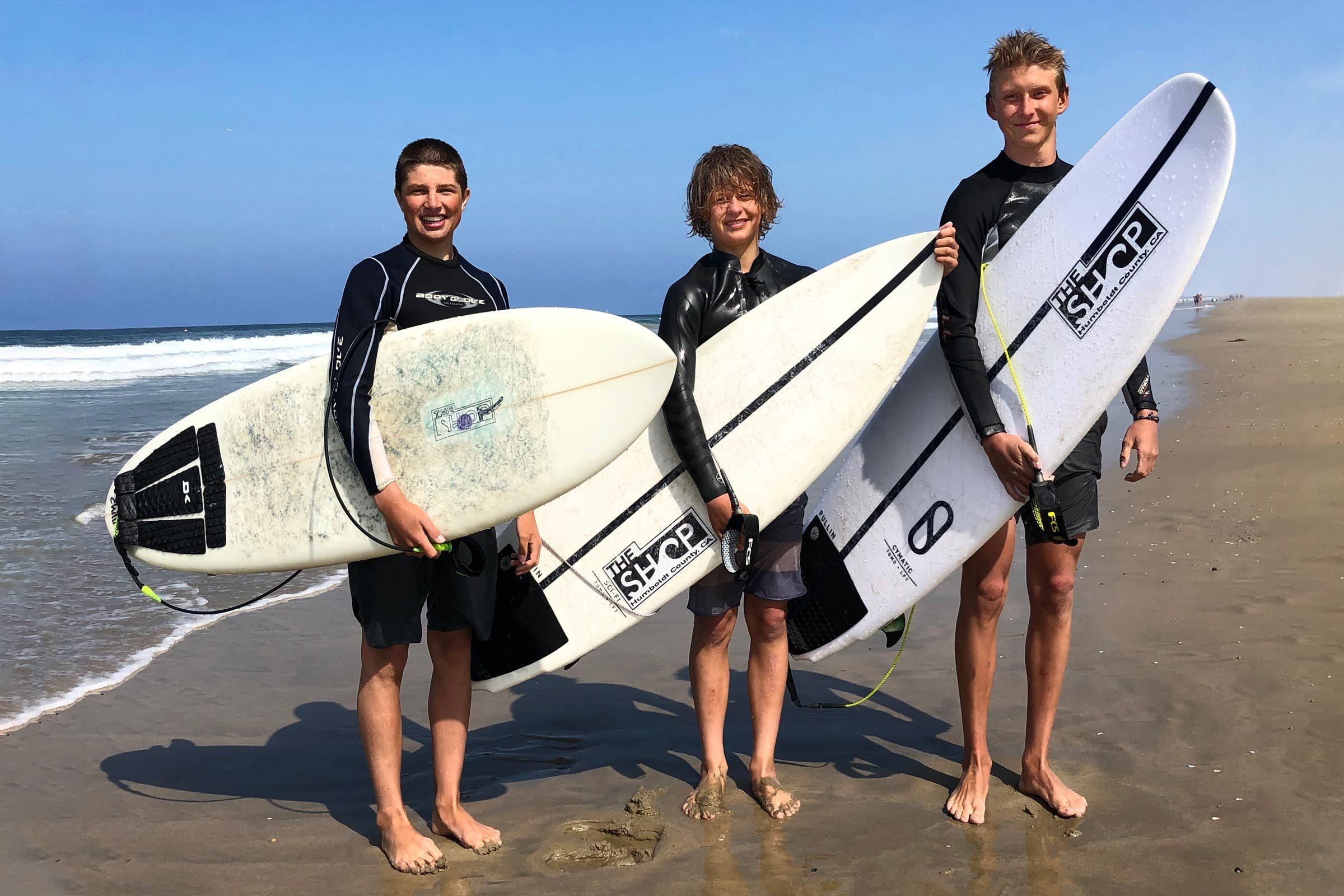 Spenvser Stratton, Taj Ortiz-Beck, and Adrian York on the beach holding surf boards