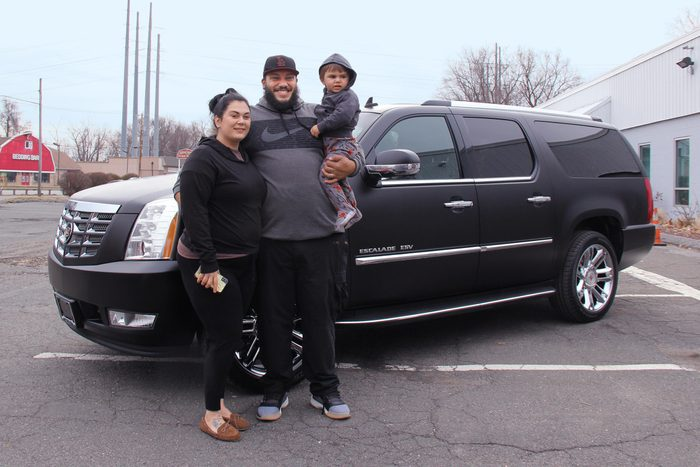 Amanda Disley, Benny Correa, and their son standing in front of their repaired vehicle