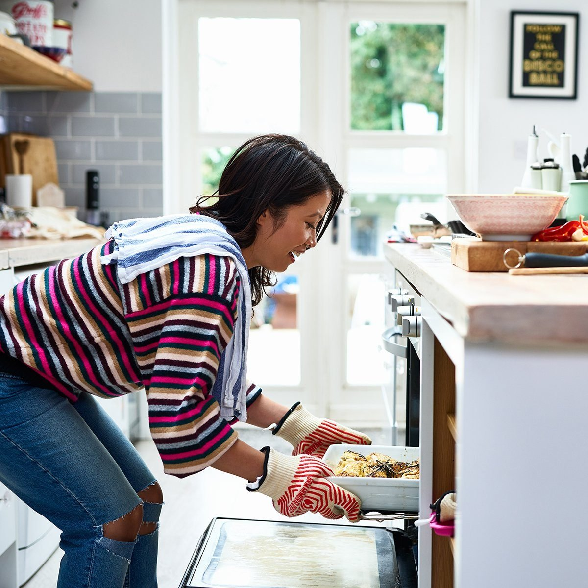 Side view of mid adult woman cooking in kitchen, bending down wearing oven gloves, smiling, satisfaction, healthy eating