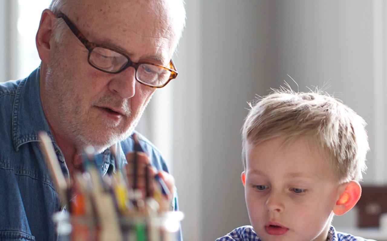grandfather helping grandson with homework. concentration, kindergarten teacher, glasses, study.