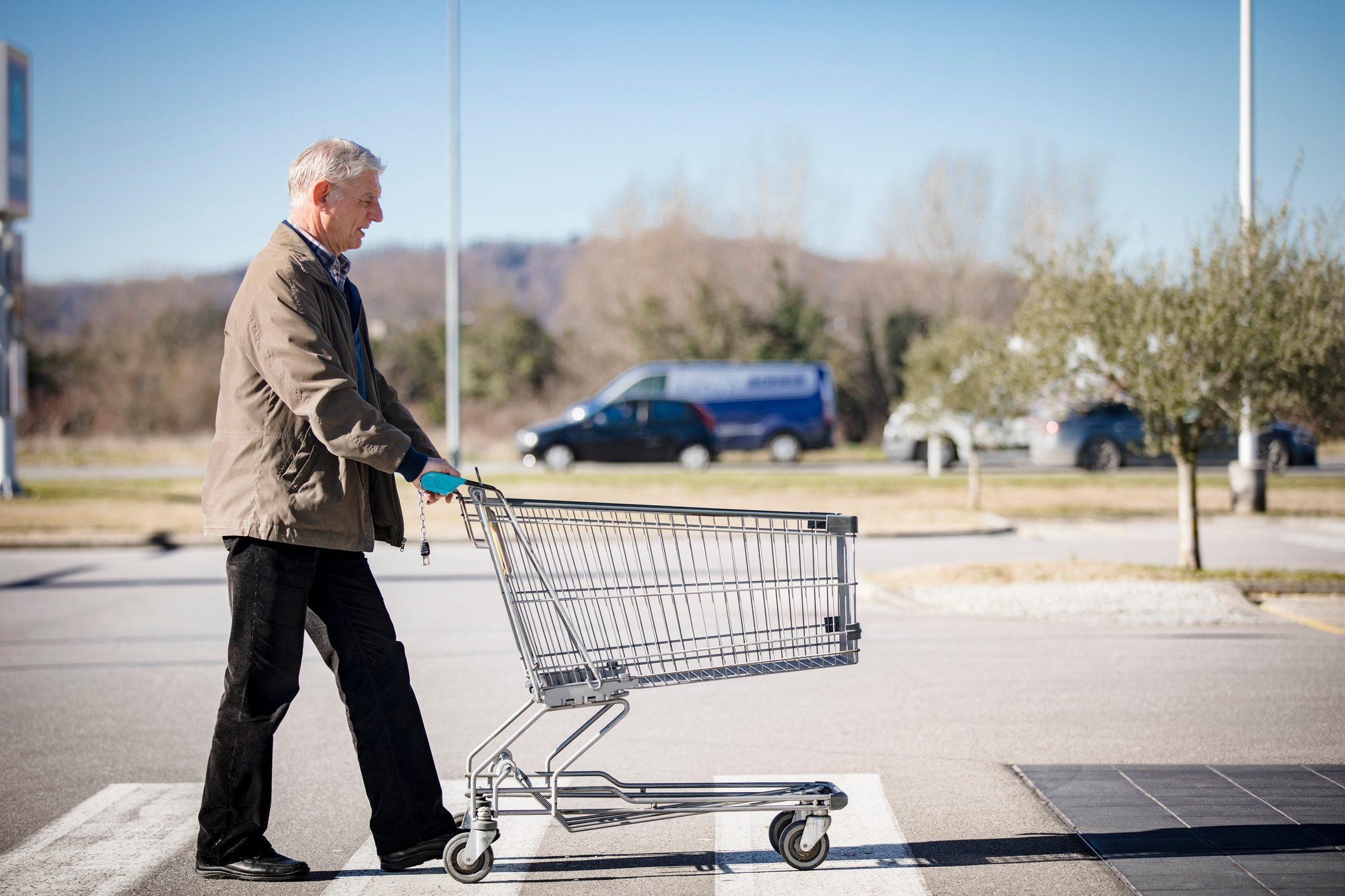 Senior Adult Man Pushing Empty Shopping Cart on Supermarket's Parking Lot