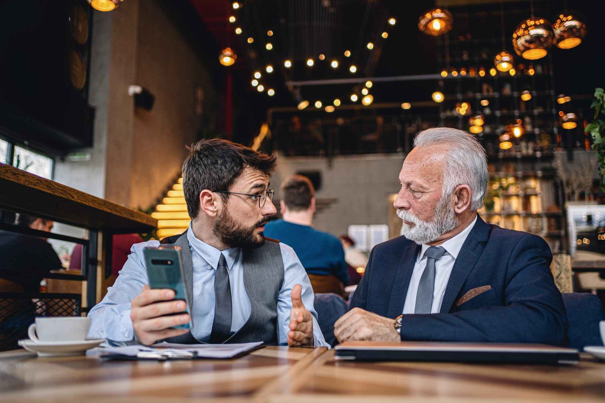 Senior businessman listening to a younger colleague's business strategy at a cafe