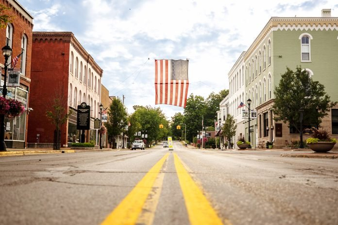a large flag flies over main street in Buchanan, Michigan; shot from the center of the road looking up