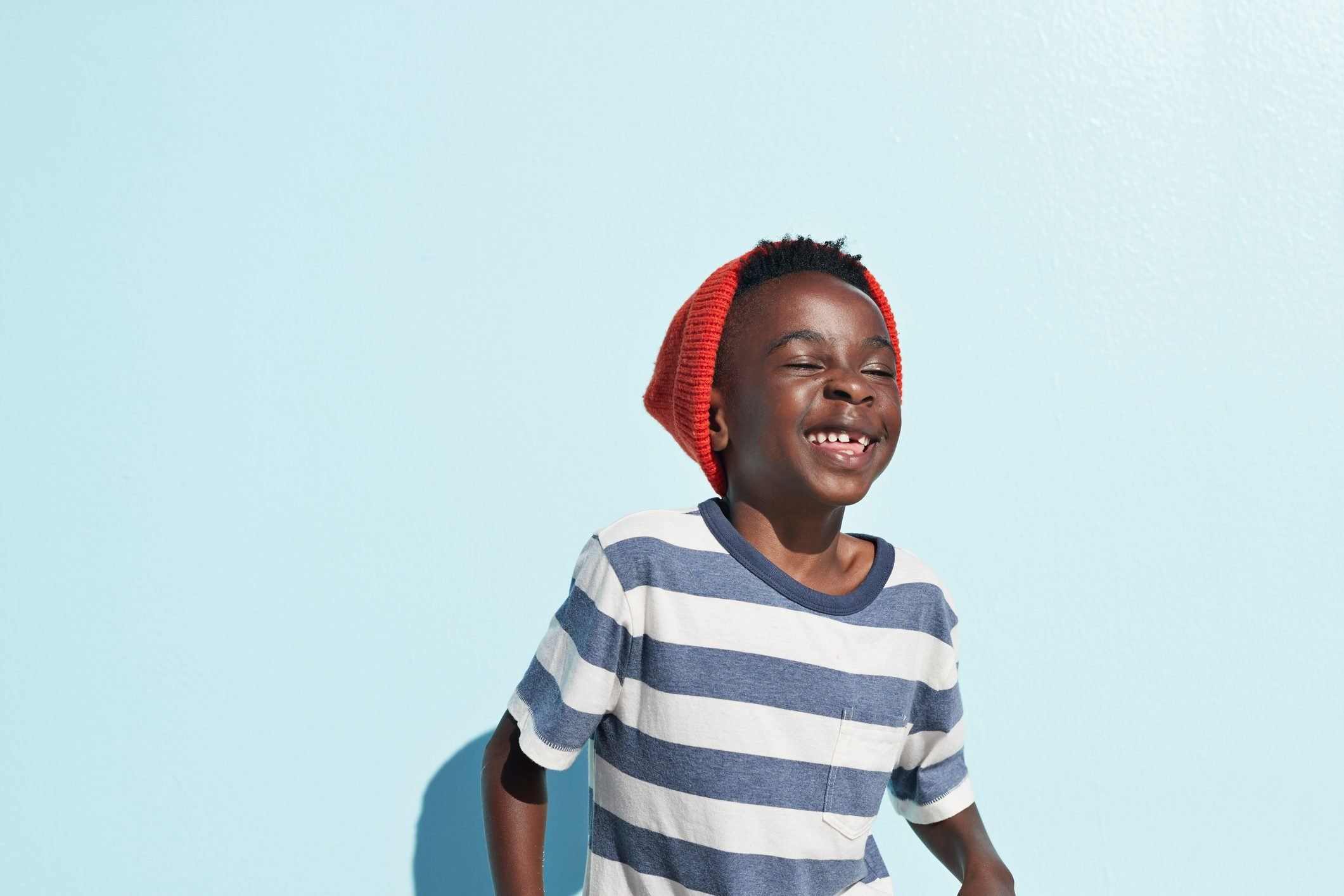 Portrait of cool boy laughing , on studio background