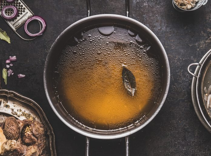 Clear broth or stock without meat in cooking pot , close up