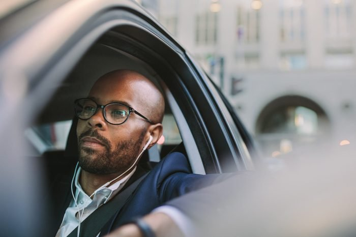 Relaxed businessman traveling by a car