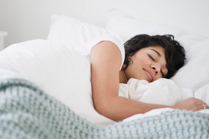 Hispanic woman sleeping in bed