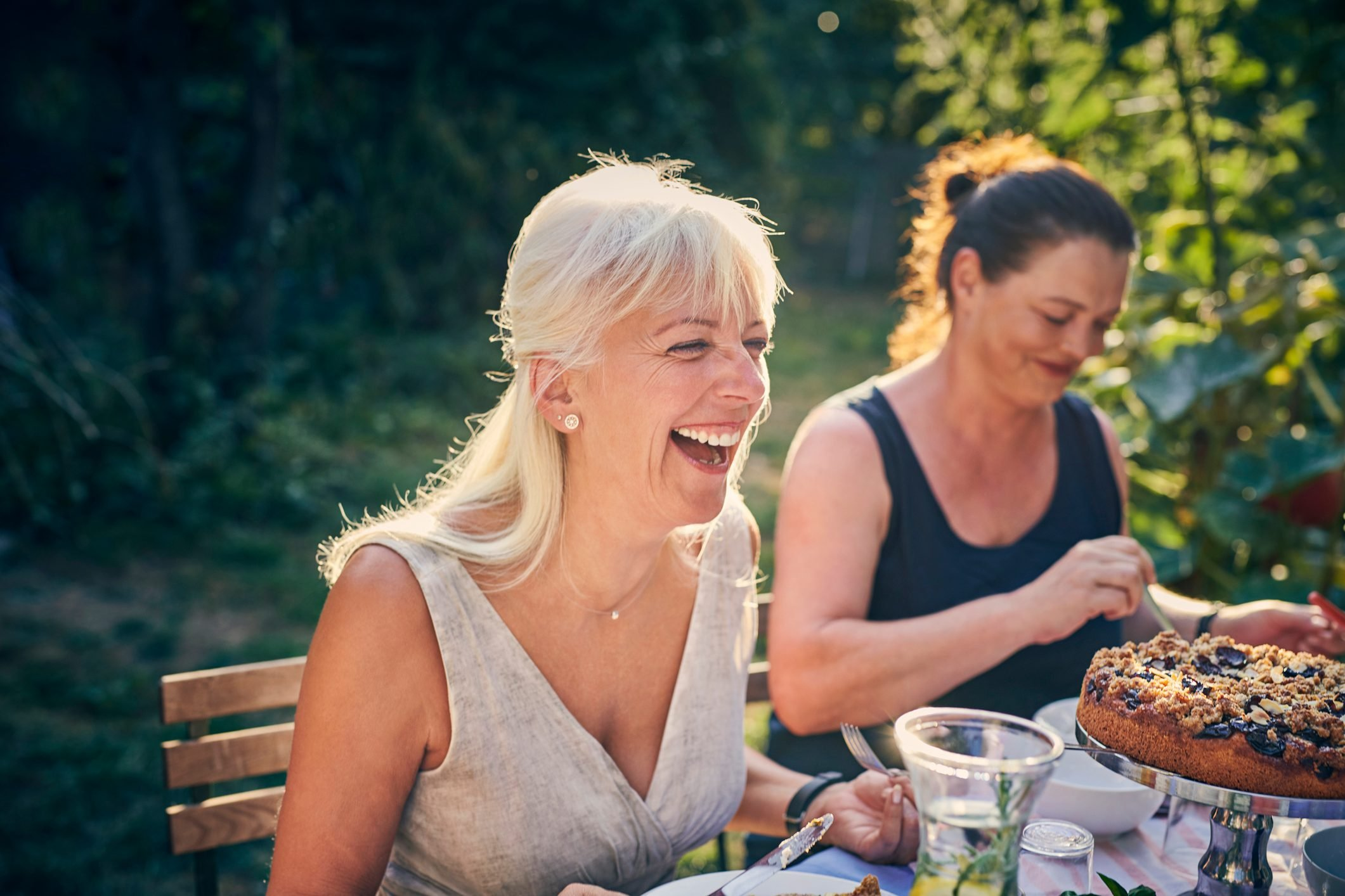 Mature woman laughing at garden party
