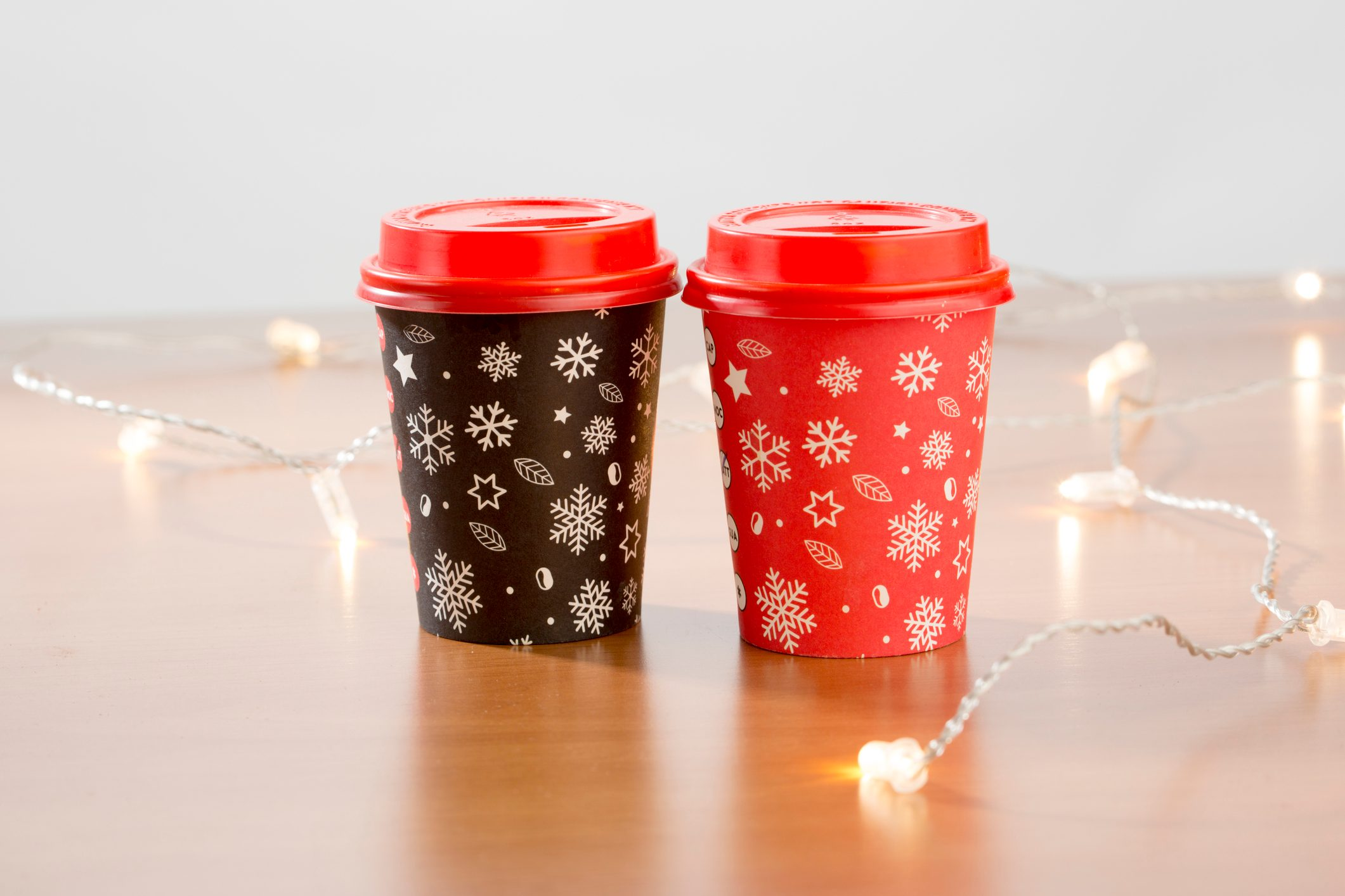 Coffee to go in red cup on black and christmas decorations