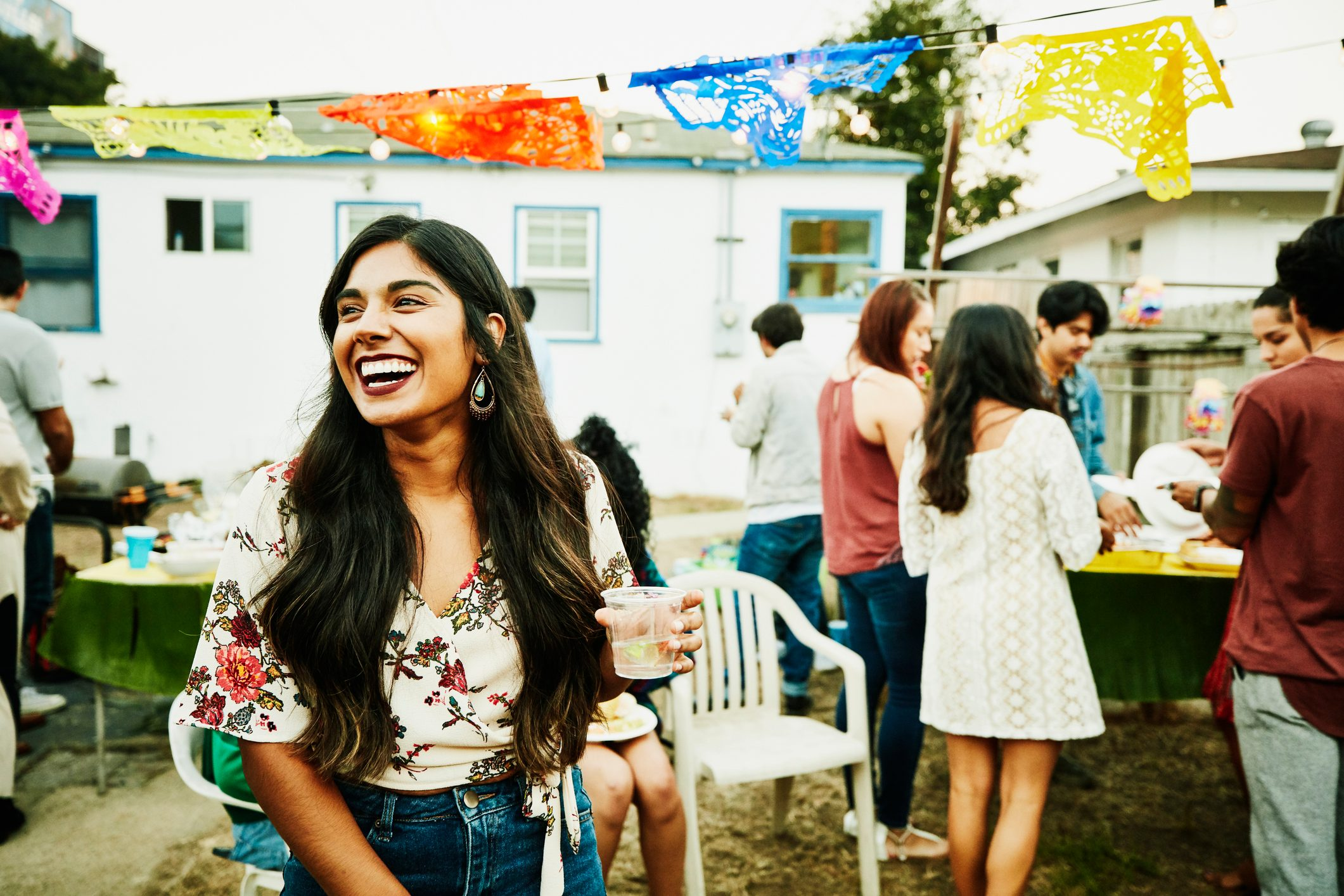 Laughing woman hanging out with friends during backyard party