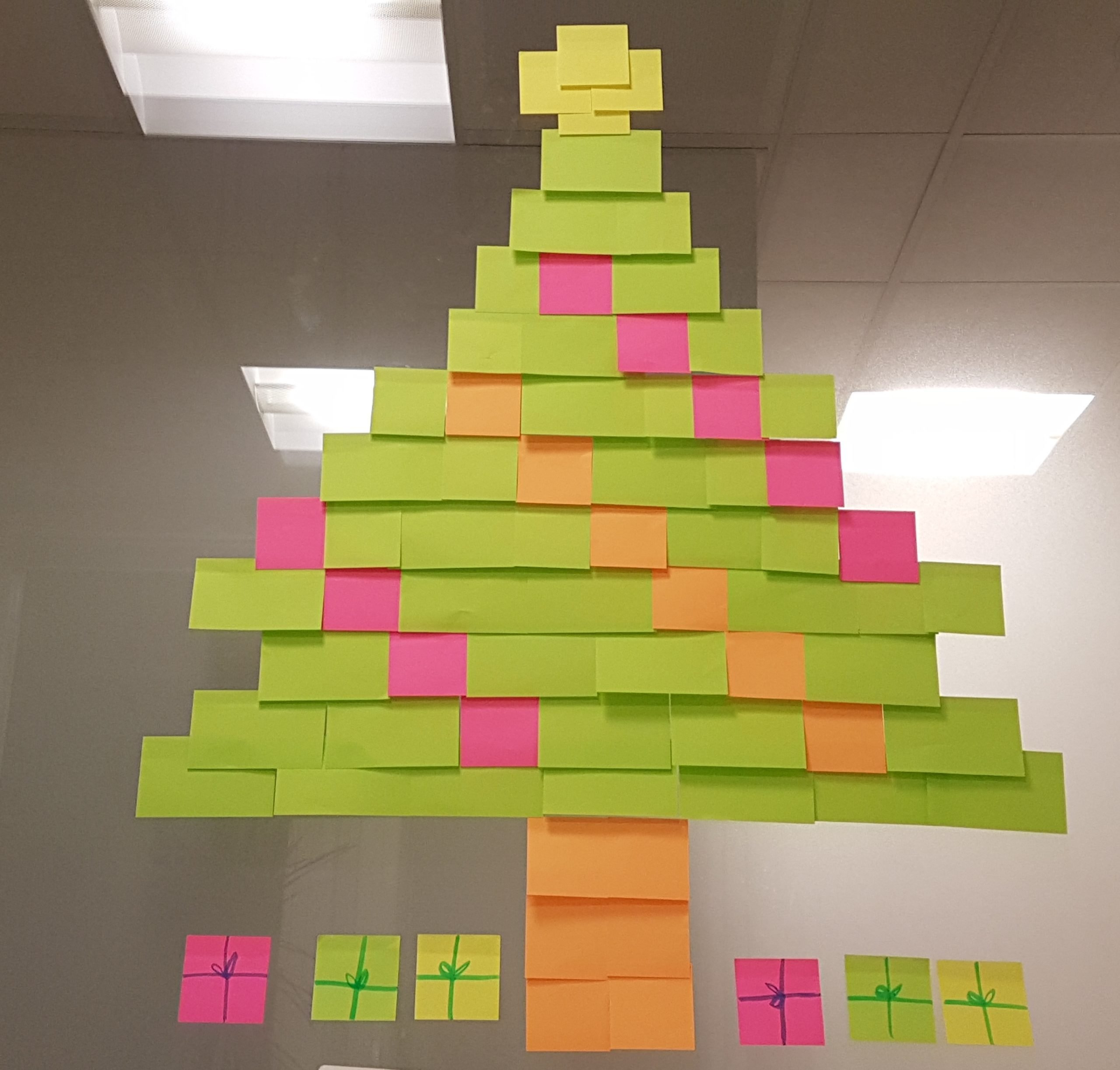 Adhesive Notes In Christmas Tree Shape On Glass Window